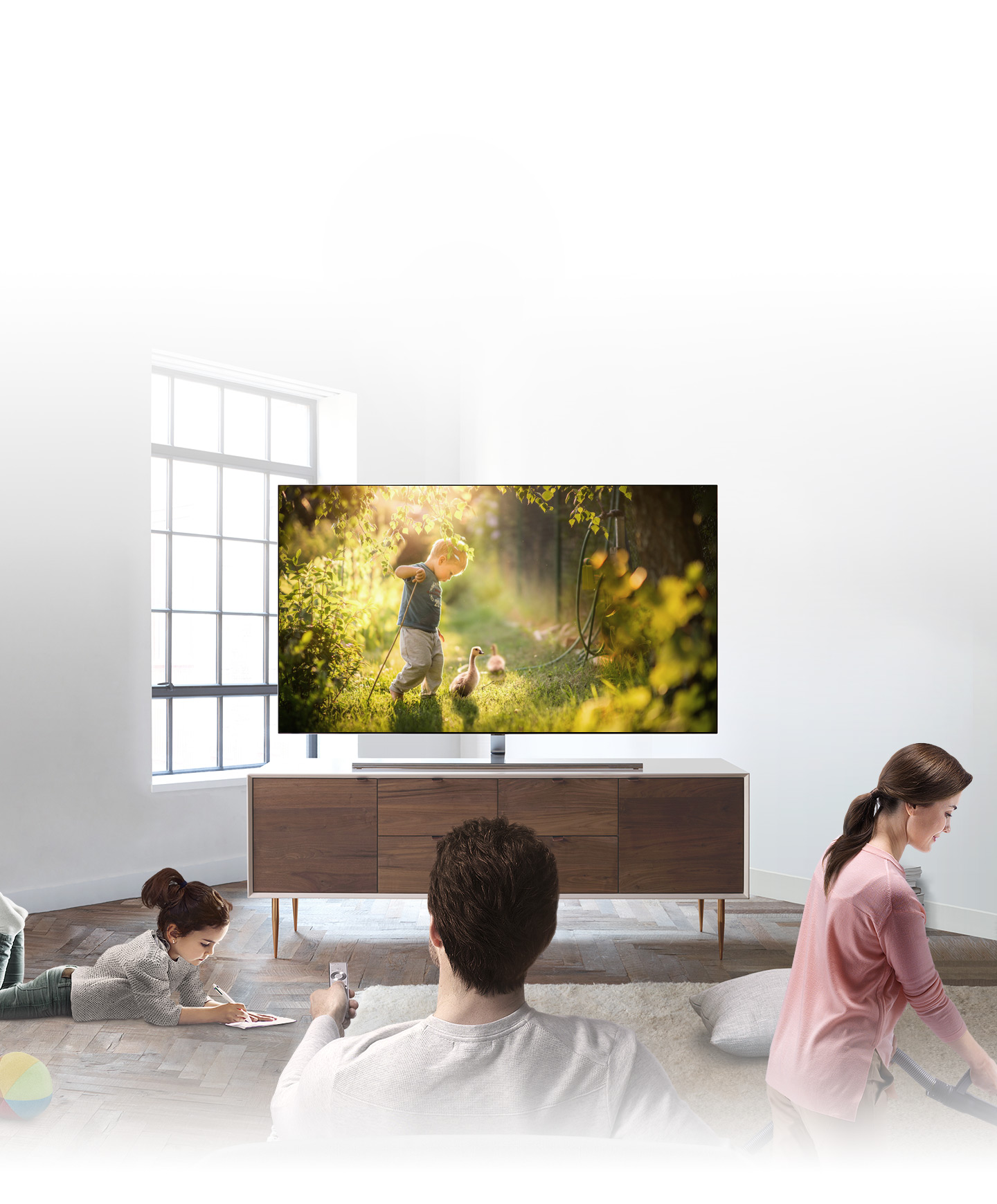 It shows father's back and he is watching QLED TV at the direct front in the living room. In the left side of the living room, a child is drawing and mom is cleaning in the right side of the living room.