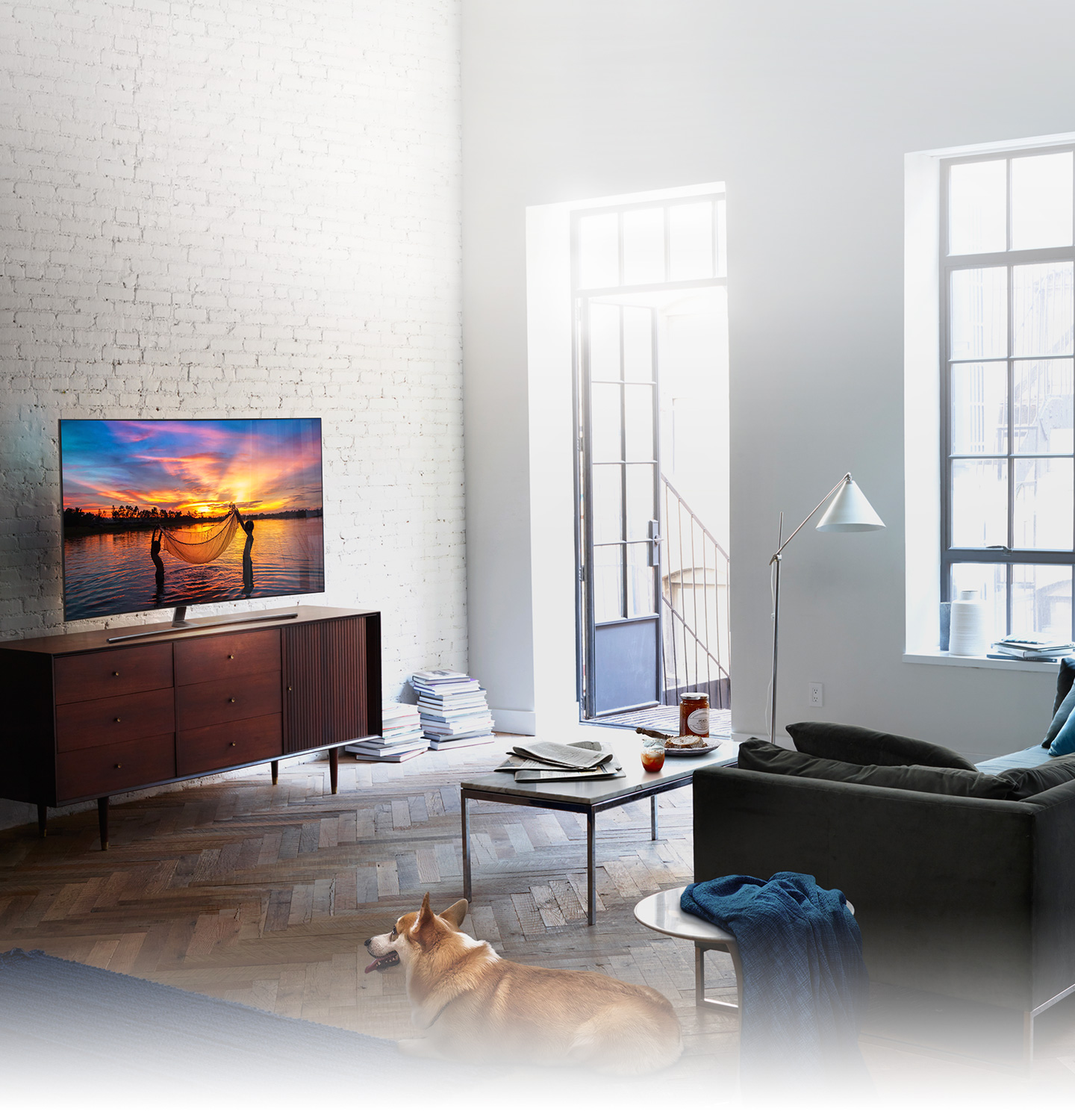 QLED TV has been set in the living room where the morning sun shines brightly and on its display shows children fishing with their net in the seashore glowing with the setting sun.