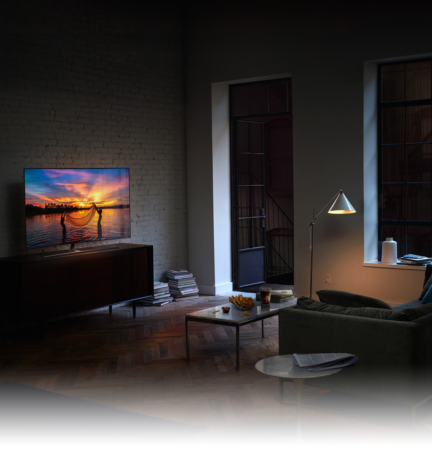 QLED TV has been set in the living room in the early evening and on its display shows children fishing with their net in the seashore glowing with the setting sun like a movie.