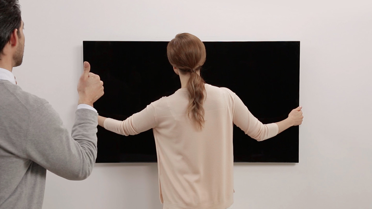 It is the figure that a couple is hanging TV in the living room together. The woman is adjusting the position of TV and the man is watching her from behind.